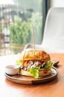 Burger de boeuf au fromage et sauce sur plaque de bois photo