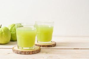 verre de jus de goyave frais avec des fruits de goyave frais sur table en bois photo