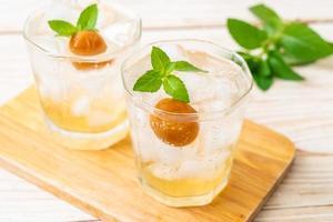 jus de prune glacé avec soda et menthe poivrée sur la table en bois - boisson rafraîchissante photo