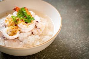 bouillie ou soupe de riz bouilli avec des fruits de mer de crevettes, de calmars et de poisson dans un bol photo