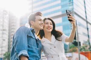 jeune couple asiatique prenant selfie ensemble dans la rue photo