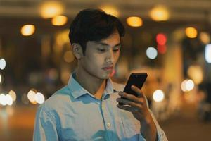 l'homme est debout à l'aide d'un téléphone portable dans le ciel le soir photo