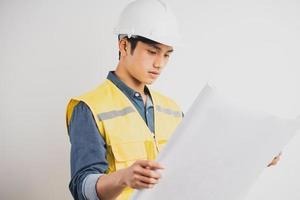 ingénieur de construction asiatique lisant le dessin technique photo