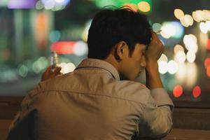homme asiatique fumant et buvant le soir photo