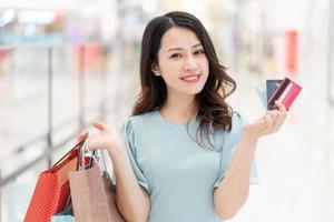 Jeune fille debout tenant une carte de crédit dans le centre commercial photo
