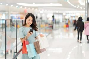jeune fille fait du shopping et utilise le téléphone au centre commercial photo