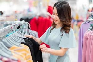 jeune fille choisit d'acheter des vêtements au centre commercial photo