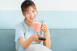 jeune femme asiatique assise sur un canapé, boire du café et regarder la télévision photo