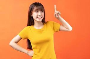 image de jeune fille asiatique portant un t-shirt jaune sur fond orange photo