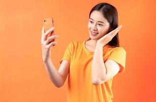 image de jeune femme asiatique tenant un smartphone sur fond orange photo