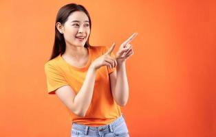 image de jeune femme asiatique portant un t-shirt orange sur fond orange photo