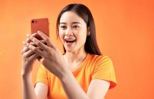 femme asiatique tenant un smartphone dans sa main avec une expression surprise photo
