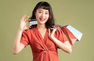 femme asiatique tenant un sac à provisions et brandissant une carte bancaire photo