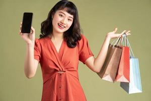 femme asiatique tenant un sac à provisions et tenant un téléphone avec un écran blanc photo