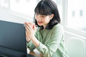belle femme d'affaires asiatique assise et buvant du café à son bureau pendant la pause déjeuner photo