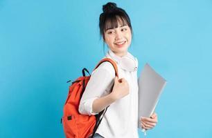 étudiante asiatique portant un sac à dos derrière son dos, tenant un smartphone, le cou portant des écouteurs sans fil, tenant une tasse en papier photo