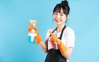 femme au foyer asiatique porte des gants orange et tient un jet d'eau dans sa main photo