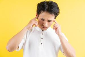 Portrait de jeune homme ayant un mal de tête sur fond jaune photo