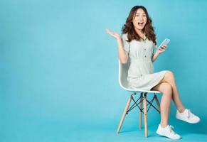 jeune fille asiatique assise sur une chaise à l'aide d'un téléphone avec une expression surprise en arrière-plan photo