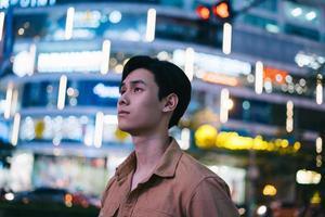 un homme asiatique marche dans la rue la nuit se sentant perdu photo