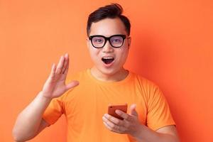 jeune homme asiatique tenant le téléphone avec une expression surprise photo