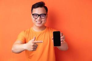 jeune homme asiatique tenant le téléphone avec une expression excitée photo