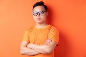 homme asiatique avec les bras croisés sur fond orange photo