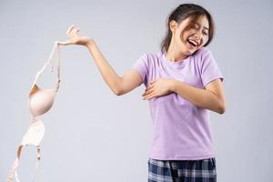 la jeune fille asiatique a enlevé son soutien-gorge avec un visage heureux photo