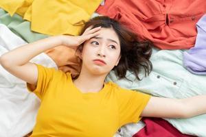 fille asiatique coincée dans son désordre de vêtements photo
