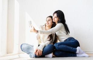 deux belles femmes prenant selfie sur téléphone mobile faisant des grimaces photo