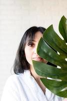 heureuse belle femme du Moyen-Orient portant des serviettes de bain tenant une feuille de monstera verte devant son visage photo