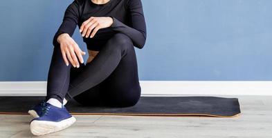 Jeune femme blonde en vêtements de sport portant des lunettes de réalité virtuelle assis sur un tapis de fitness à la maison photo