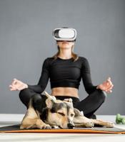 Jeune femme en vêtements de sport portant des lunettes de réalité virtuelle assis sur un tapis de fitness avec chien photo