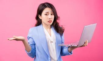 femme d'affaires asiatique tenant un ordinateur portable sur fond rose photo