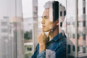 l'homme asiatique contemplait par la porte vitrée photo