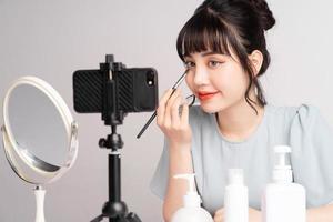 jeune femme asiatique en direct pour enseigner le maquillage en ligne photo