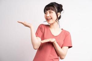 jeune femme asiatique posant sur fond blanc, utilisant le doigt pour pointer et montrer, geste de la main photo