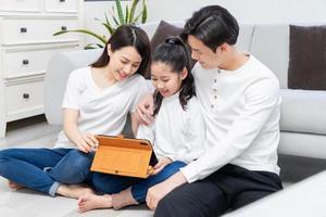 les parents asiatiques guident leur fille à utiliser la tablette photo