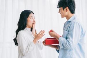 une fille asiatique se sent heureuse et surprise de recevoir des cadeaux de son petit ami le jour de la saint valentin photo