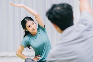 couple asiatique faisant du yoga ensemble à la maison photo