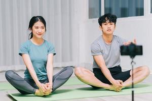 un entraîneur personnel asiatique guide les étudiants en yoga et en enregistrement vidéo pour enseigner le yoga en ligne photo