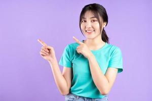 jeune fille asiatique en chemise cyan posant sur fond violet photo