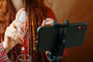 femme pulvérise un antiseptique sur son smartphone. photo