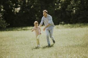 père pourchassant sa petite fille en jouant dans le parc photo