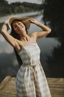 détente jeune femme debout sur une jetée en bois au bord du lac photo