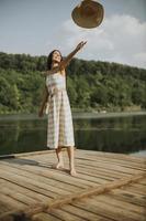 heureuse jeune femme debout sur une jetée en bois au bord du lac photo
