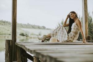 jeune femme relaxante sur une jetée en bois au bord du lac photo