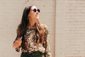 Portrait d'une jeune femme joyeuse souriante à l'extérieur avec des lunettes de soleil en détournant les yeux photo