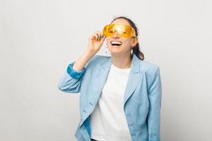 photo de joyeuse jeune femme souriante en tenue de soirée portant de grandes lunettes jaunes, drôle de jeune femme