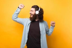 joyeux bel homme hipster barbu écoutant de la musique au casque sans fil blanc. photo
